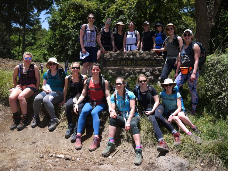 Image shows the group of fifteen women ready to set off climbing Mount Kilimanjaro via the Rongai Route.  The group is standing around a stone sign that says Nal'emuru Route.