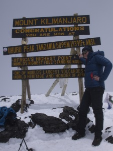 Photo shows Rebecca leaning against the sign board for Uhuru Peak Mount Kilimanjaro. Rebecca is wearing sunglasses, black hiking trousers and a blue Rab down jacket. There is snow on the ground.