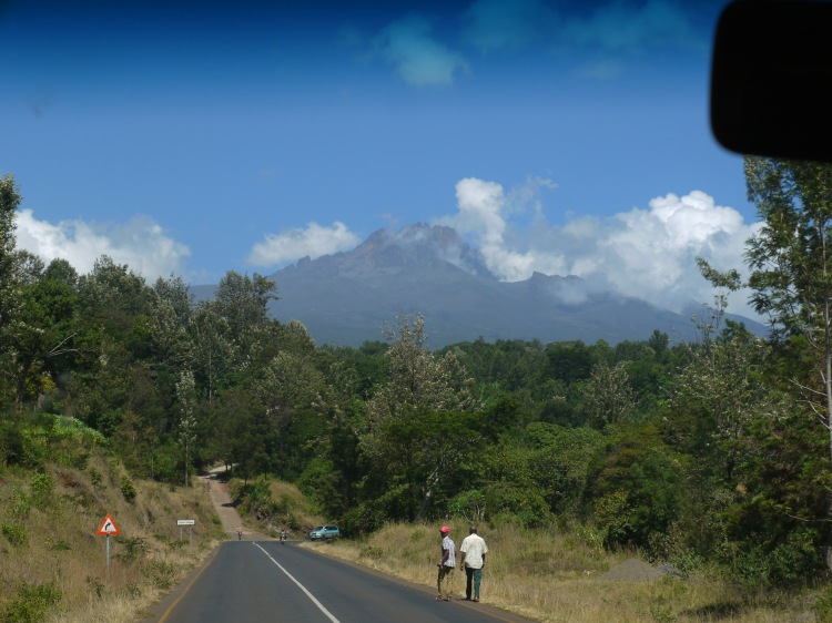 Image shows two men waking beside a road in Tanzania with Mount Kilimanjaro in the distance, partly covered by clouds.