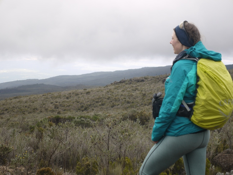 Image shows Rebecca looking across the moorland on the way from Simba Camp to Kikelelwa Camp.  There are low rain clouds in the distance and Rebecca is wearing a green waterproof and there is a florescent yellow raincover over the backpack she is carrying.