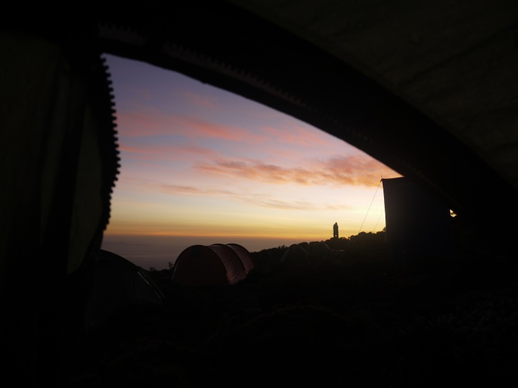 Image shows a triangle of purple and yellow sky streaked with pink clouds as dawn breaks over Kikelelwa Camp on Mount Kilimajaro.  The image is framed by the canvas of the tent and other tents can be seen in the foreground.