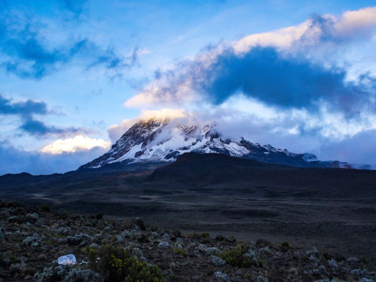 Image shows Kibo peak of Mount Kilimanjaro in Kilimanjaro National Park, Tanzania from the route to Horombo Camp.  Snow and storm cloud partially cover the peak.