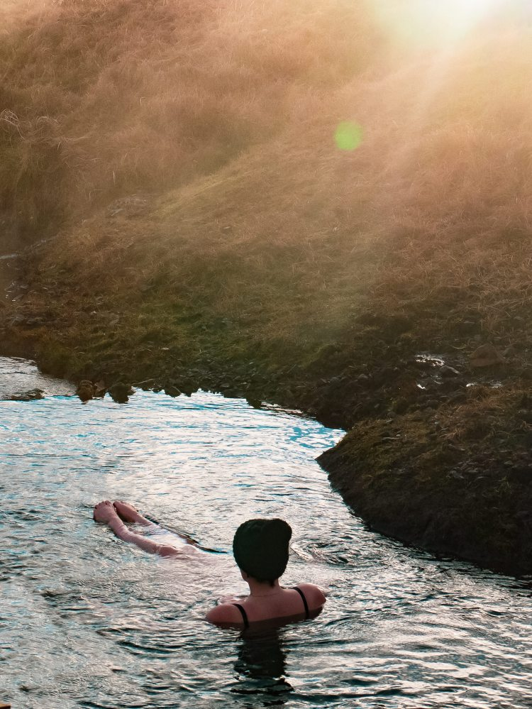 Image shows Rebecca sat in the Reykjadalur River.  Rebecca is sat facing away from the camera and wearing a black bobble hat.