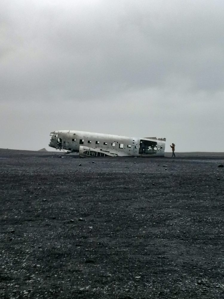 Image shows the wreck of a US Navy DC-3 plane on Solheimasadur black sand beach on the south coast of Iceland.  The photo is in colour but appears black and white.