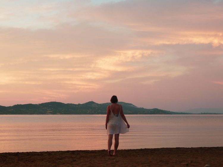 Image shows Rebecca stood on Lixouri Town beach, face towards the Bay of Argostoli at sunset.