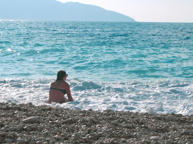 Image shows Rebecca sat in the surf of Myrtos Beach Kefalonia, Greece