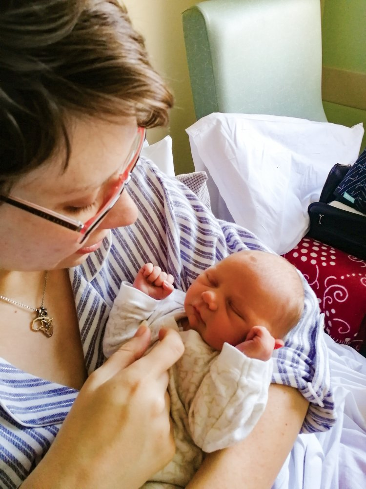 Image shows Rebecca cradling newborn baby R on the hospital ward following her positive cesarean section breech birth