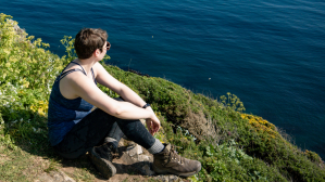 Image shows Rebecca hiking the South West Coast Path while in the early stages of pregnancy. Rebecca is sat on a cliff top surrounded by wildflowers and looking out to sea